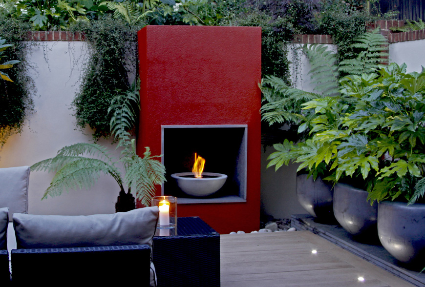 greencube plays with scale using large pots on a granite plinth in this modern garden in caterham, surrey