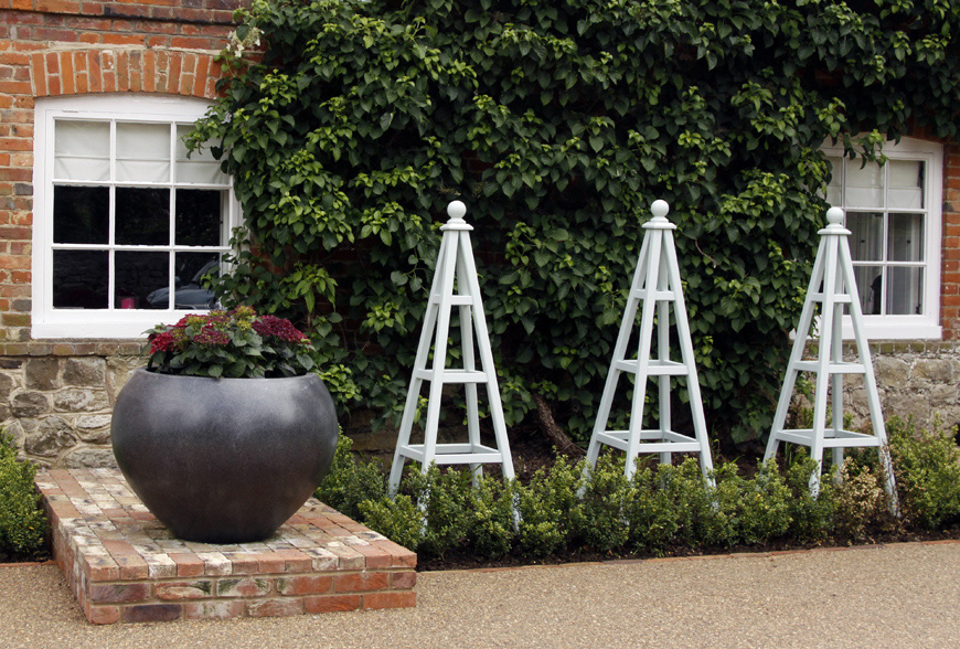subtly painted obelisks bring height to the planting borders in this sevenoaks, kent garden design by greencube